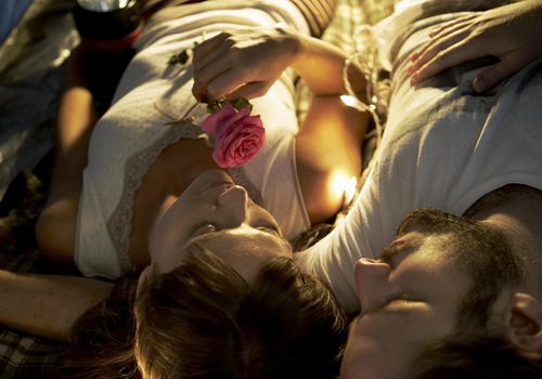 Young couple lying on back, woman holding rose flower, thinking about how to cope with infertility