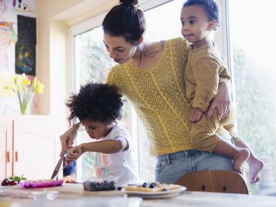 Mother helping toddler daughter cutting breakfast waffles