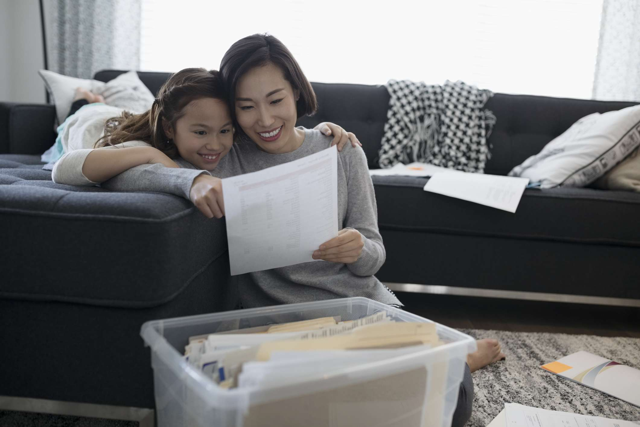 Mother and daughter viewing financial paperwork in living room