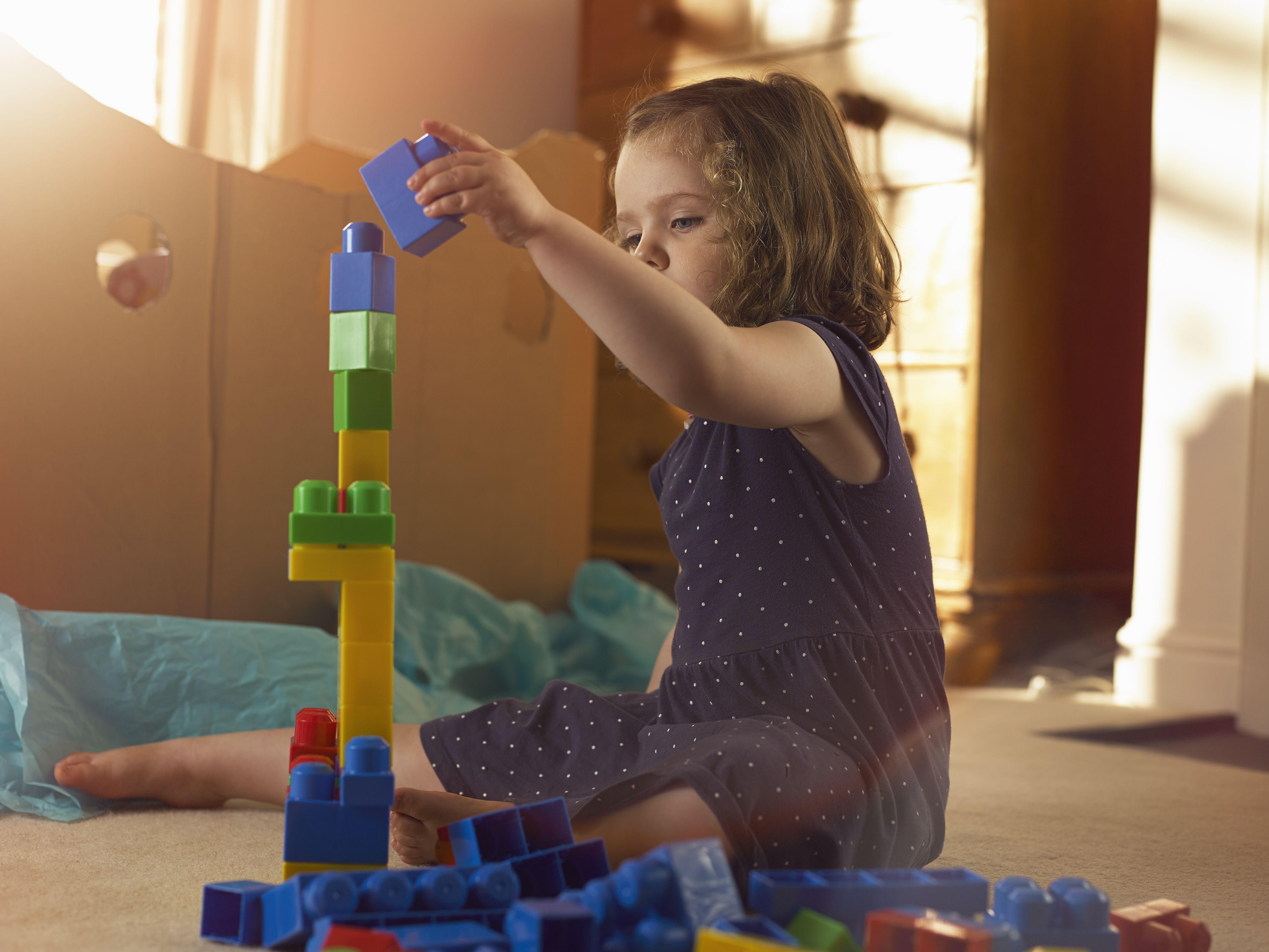 3 year old girl stacking blocks in bedroom