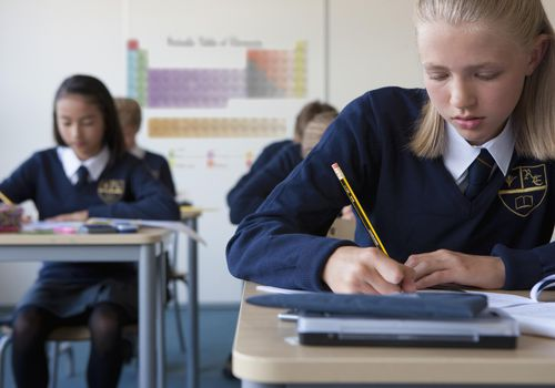 Female student in school uniform taking exam at desk in classroom