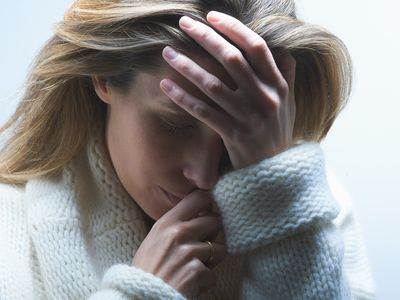 Woman in sweater holding her head, feeling depressed and anxious due to infertility