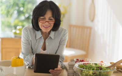 USA, New Jersey, Jersey City, Senior woman holding digital tablet while preparing salad