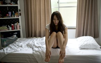 Pensive woman sitting on bed alone