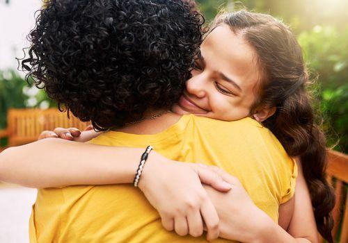 Happy teenage girl hugging her mom