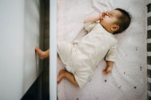 Cute Asian baby girl sucking thumb while sleeping peacefully in baby cot - stock photo