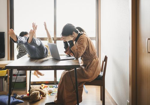 mom puts her head in her hands at the kitchen table