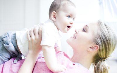 Teenage girl holding baby boy, close up.