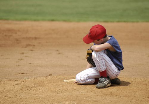 Disappointed boy bending down on baseball field