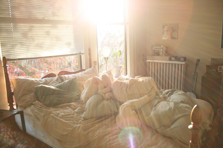 Sunlight shining through the window of a messy bedroom