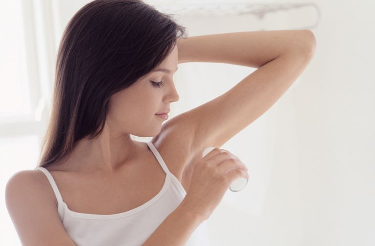 Woman applying deodorant to underarm