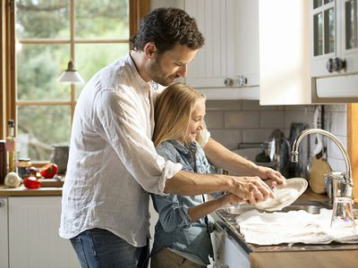 Father washing dishes with his daughter