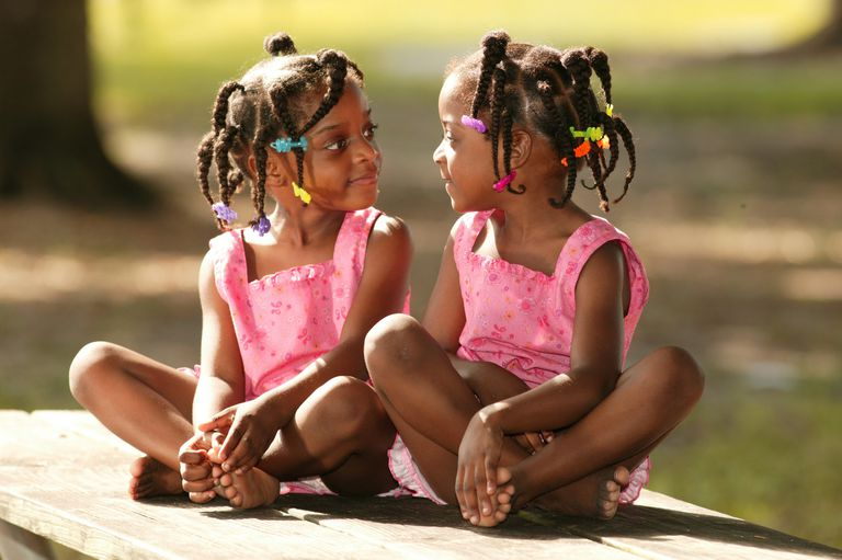 Twin sisters sitting on picnic table