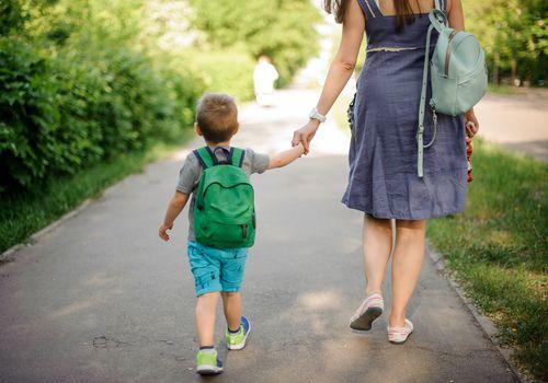 Preschooler walking to school with mom