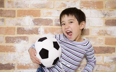 Soccer skills and more indoor games for kids - portrait of boy with soccer ball