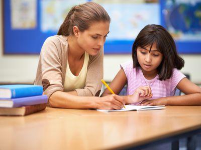 teacher helping female student with homework