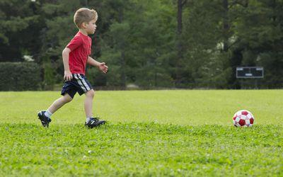 Mixed race boy playing soccer