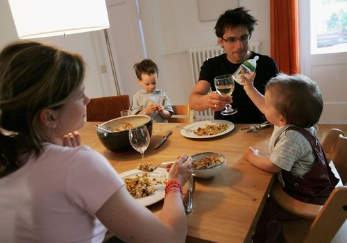Mother and father sitting at the table with a baby and toddler