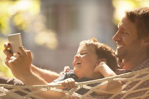 Father and son using digital tablet in hammock