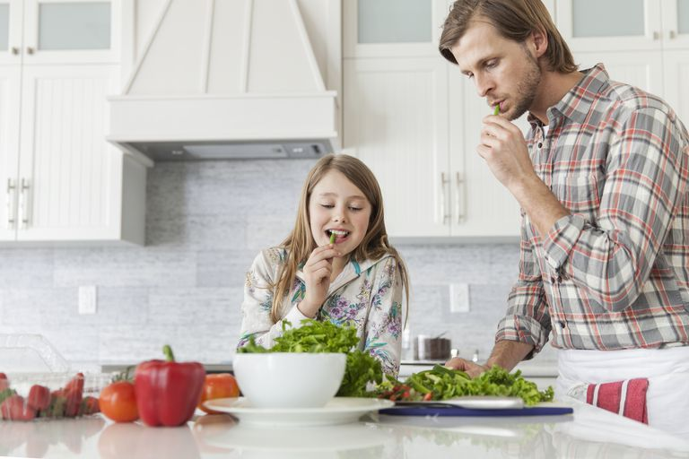 Father and daughter tasting food at kitchen island