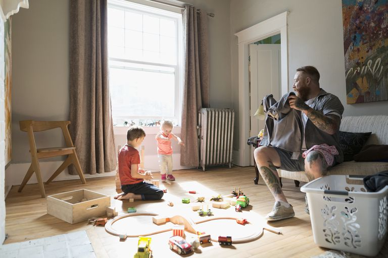 Father folding laundry near children playing with toy train and wood blocks