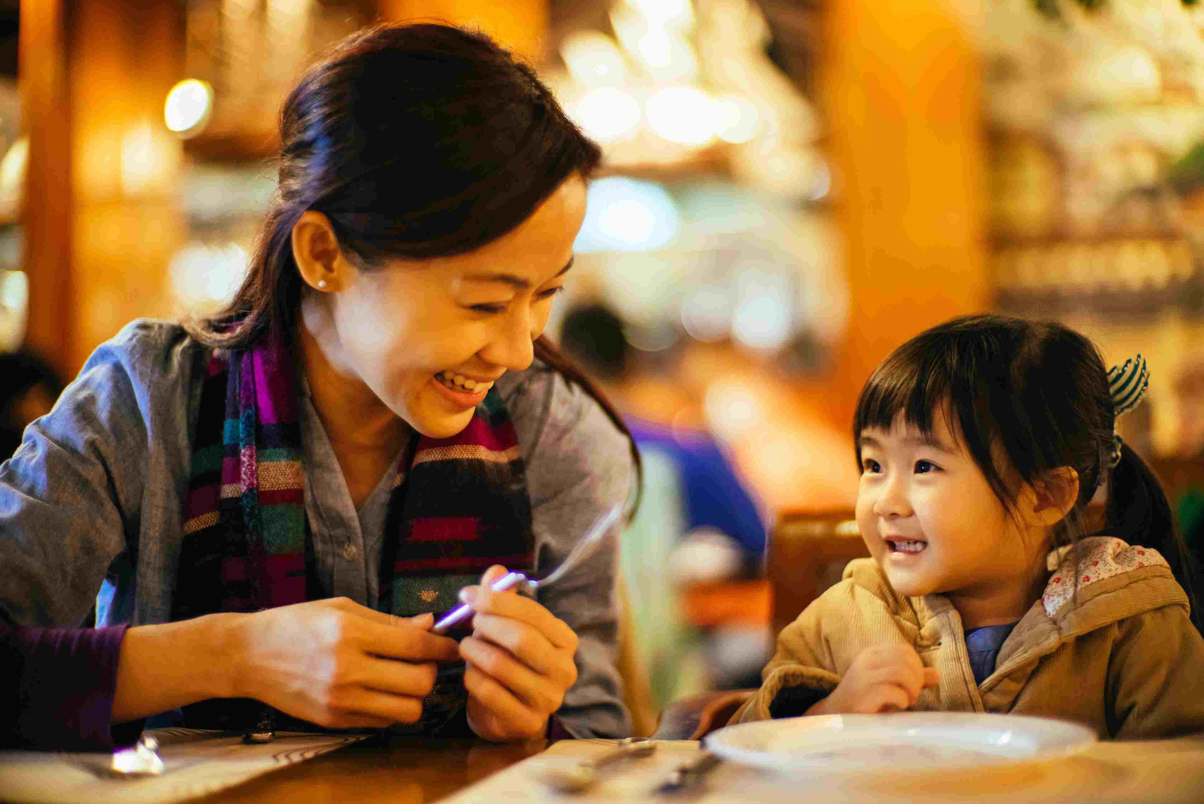 Mom & toddler girl talking joyfully in restaurant