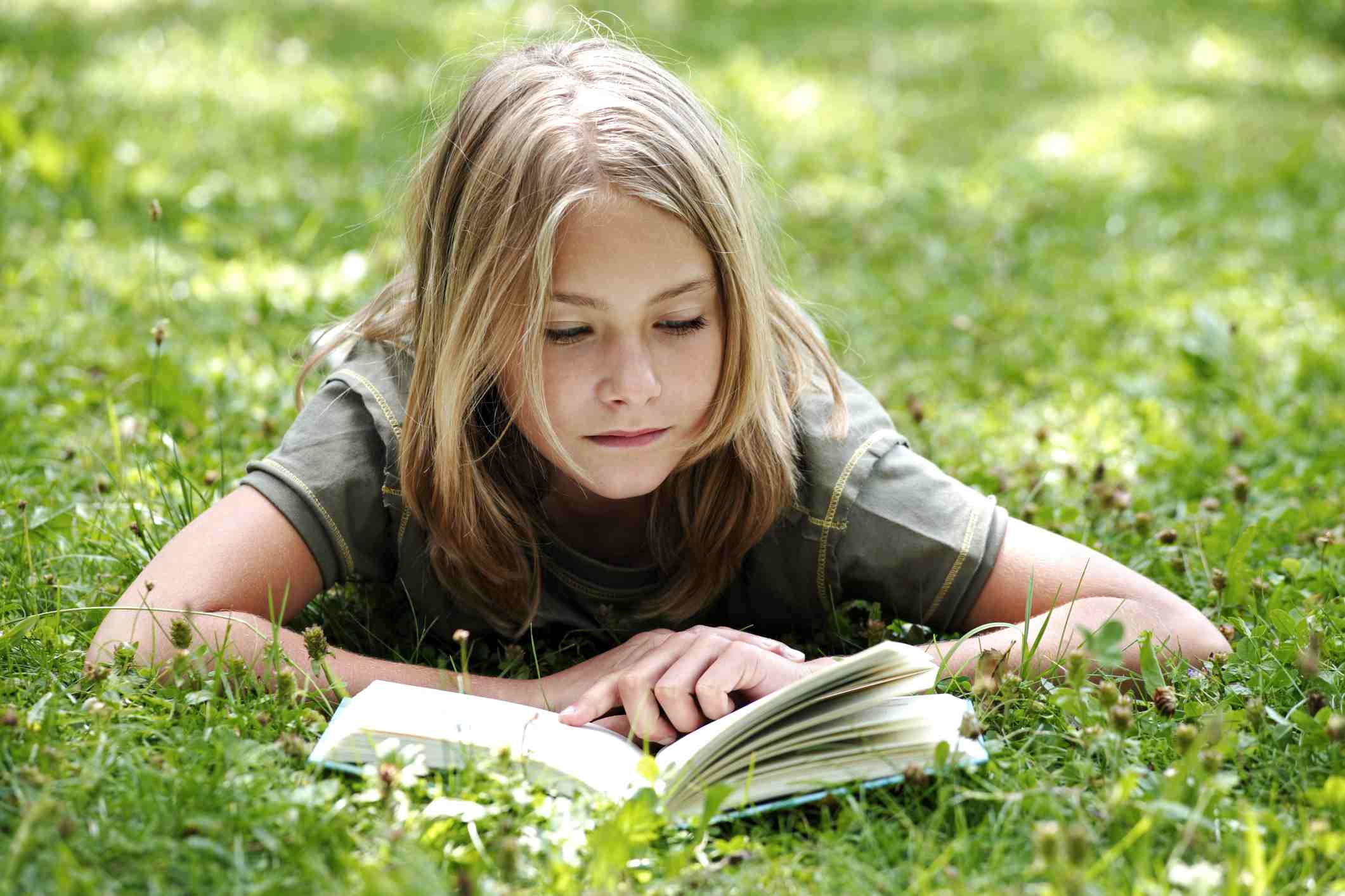 Young girl reading a book in the grass