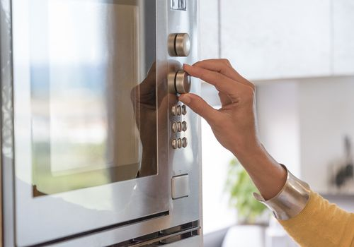 woman's hand touching dial on microwave oven