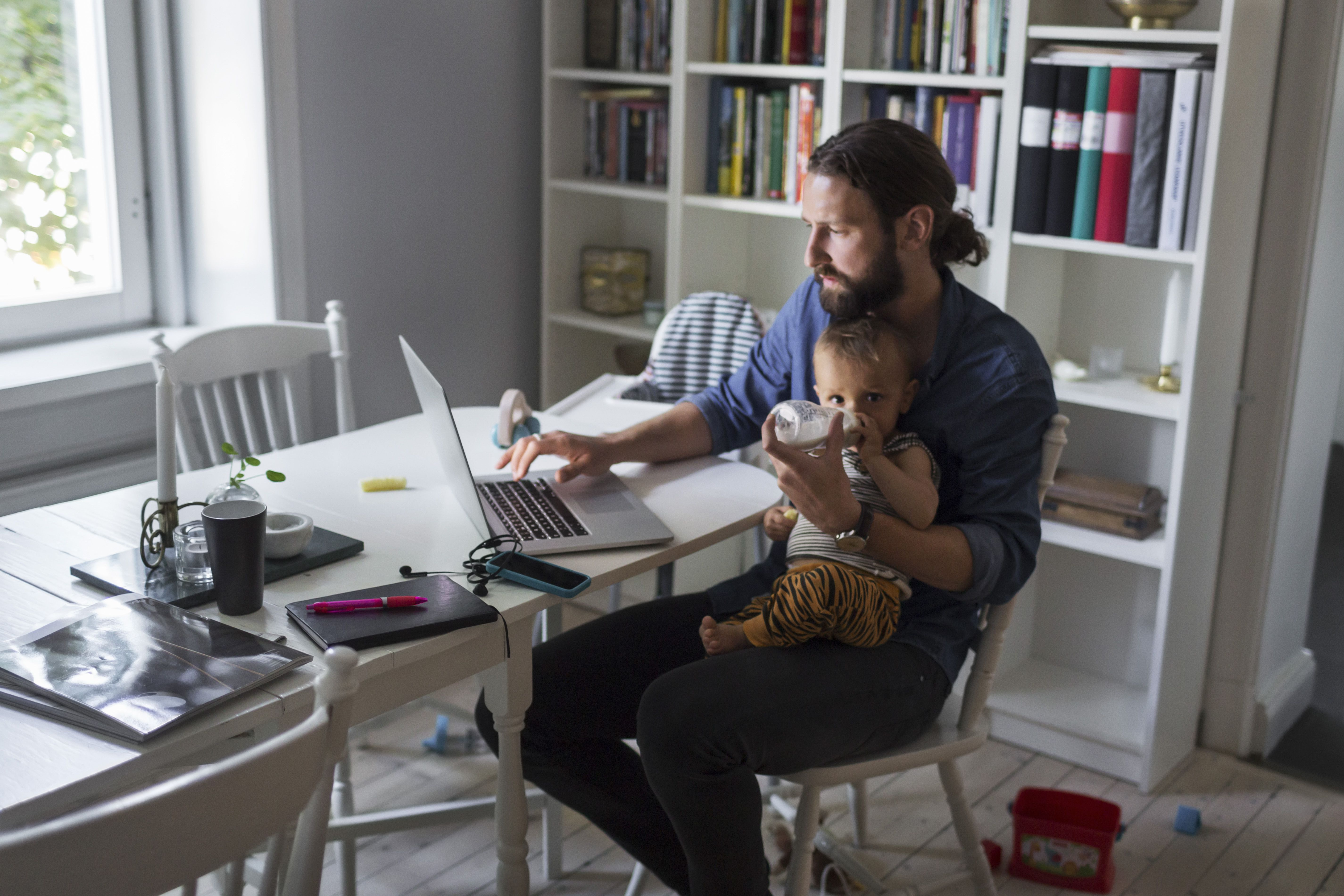 Father feeding baby boy while using laptop at home