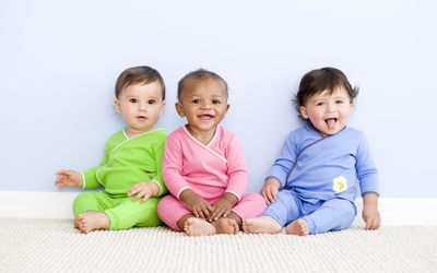 Three babies in green, pink, and blue outfits.