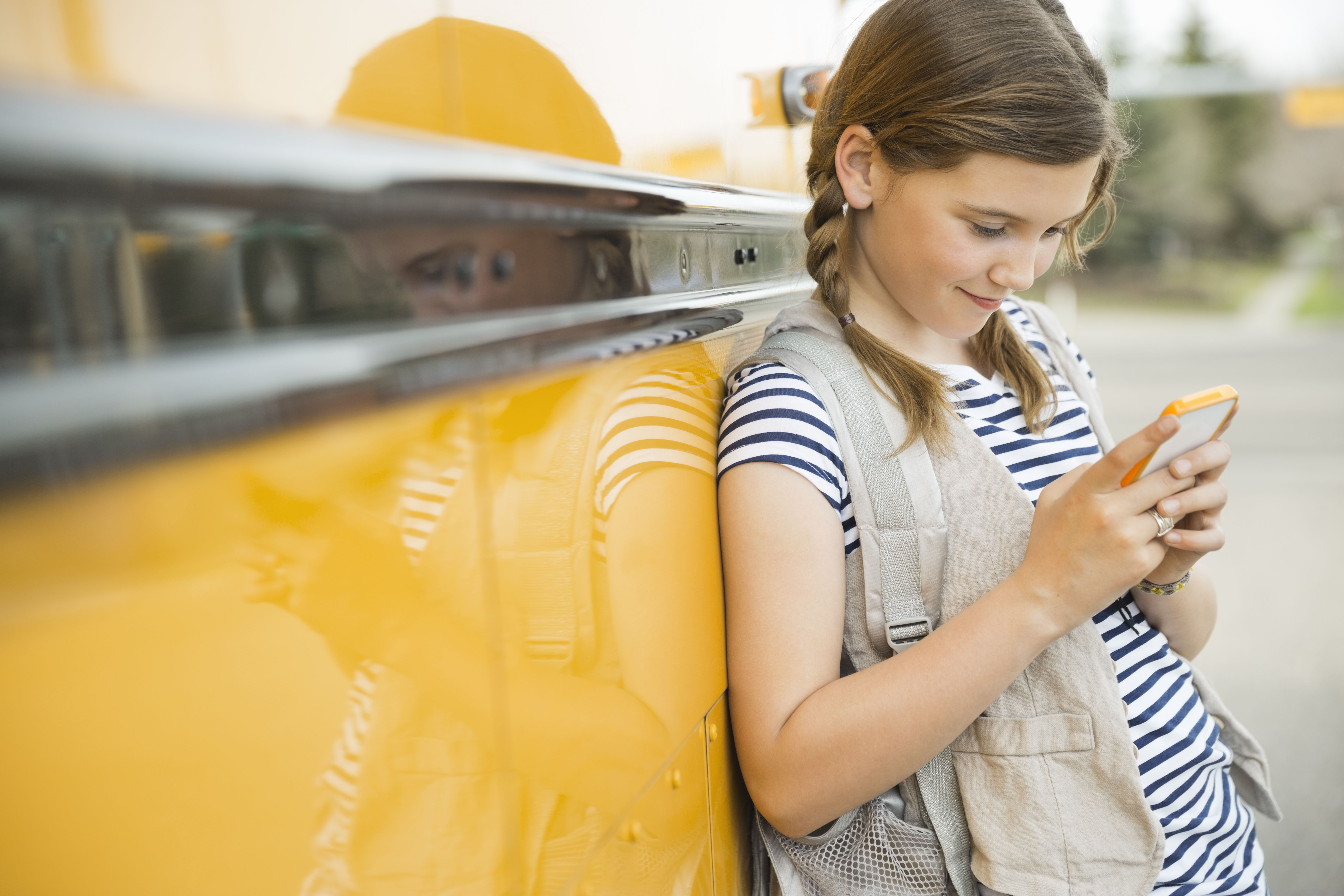 Girl leaning against school bus looking at cell phone
