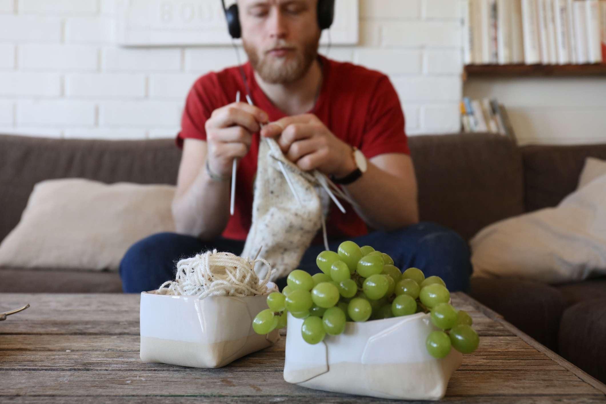 Young man knitting at home
