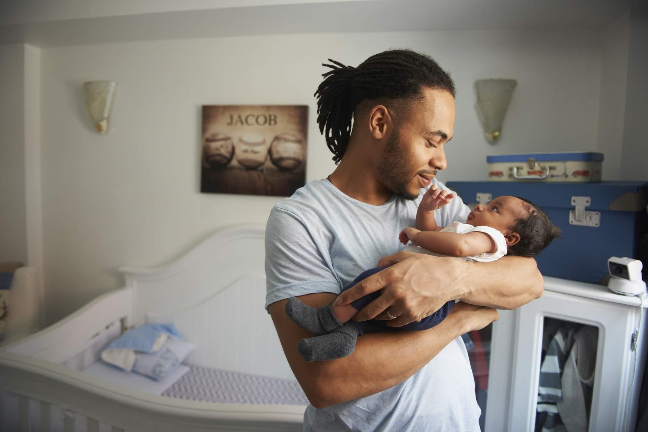 Father cradling newborn baby in nursery