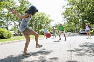 Girl kicking kickball in game