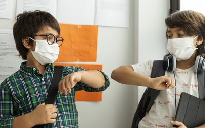 Two students wearing masks and holding school items bump elbows.