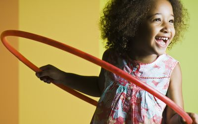 A smiling little girl playing with a hula hoop