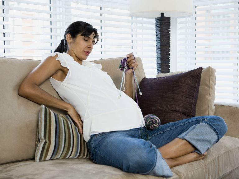 Pregnant woman knitting on a couch