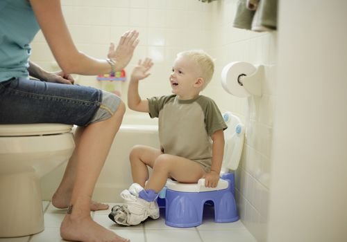 Young boy on potty seat giving his mom a high five