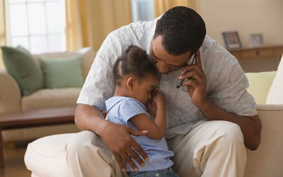 Father hugging daughter while on cell phone