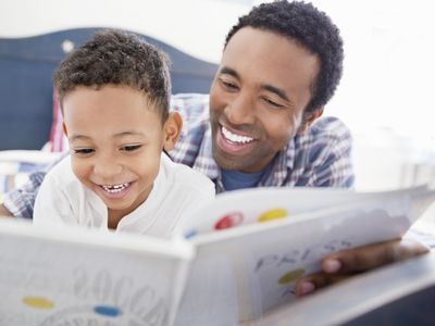 Happy father and son reading book together in bed