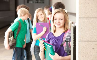middle school girl at locker with others in back