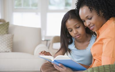 Young girl and mother reading on sofa