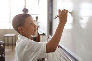 boy writing on board in classroom