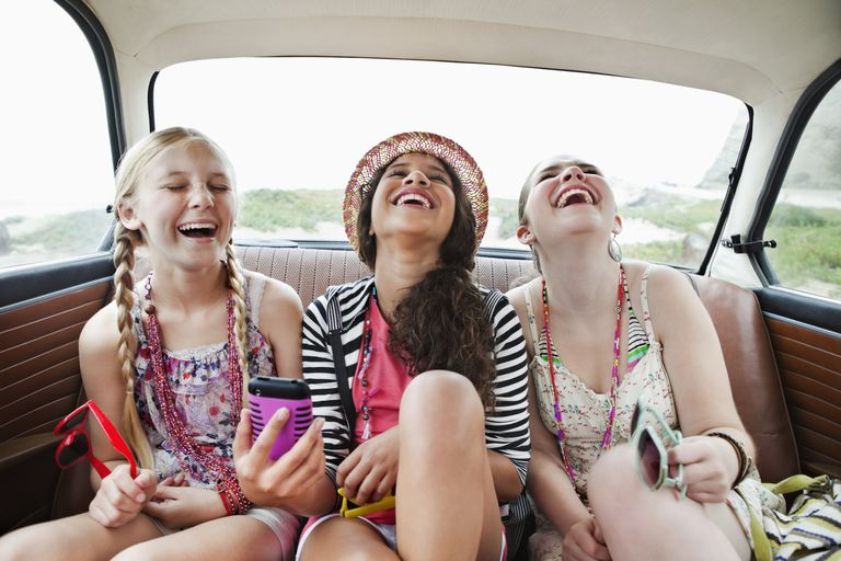 Three tween girls laughing in the backseat of a vehicle
