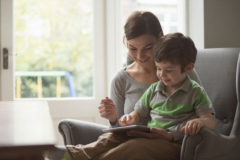 Boy sitting on mother's lap and using digital tablet