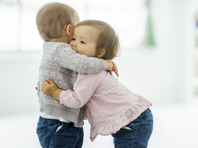 Two twin baby girls hugging each other