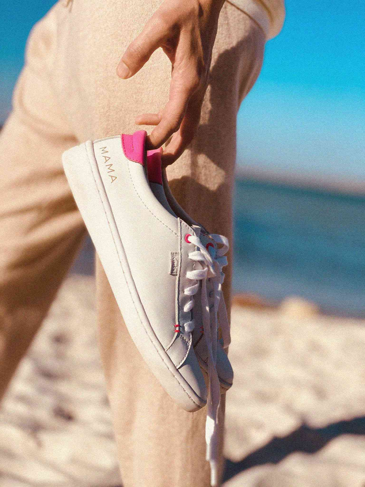 woman carrying pink and white keds