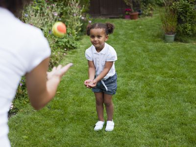 Motor planning definition: Young girl catching ball