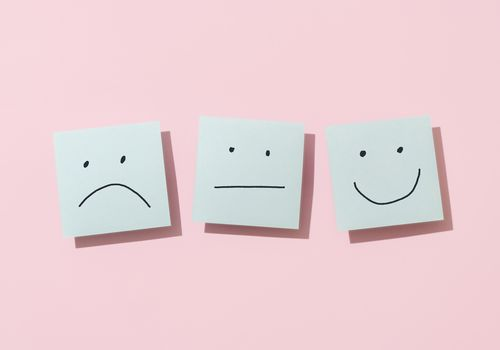 Directly above view of three blue sticky blank notes on pink background