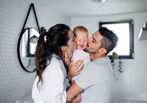 Couple holding and kissing their baby.
